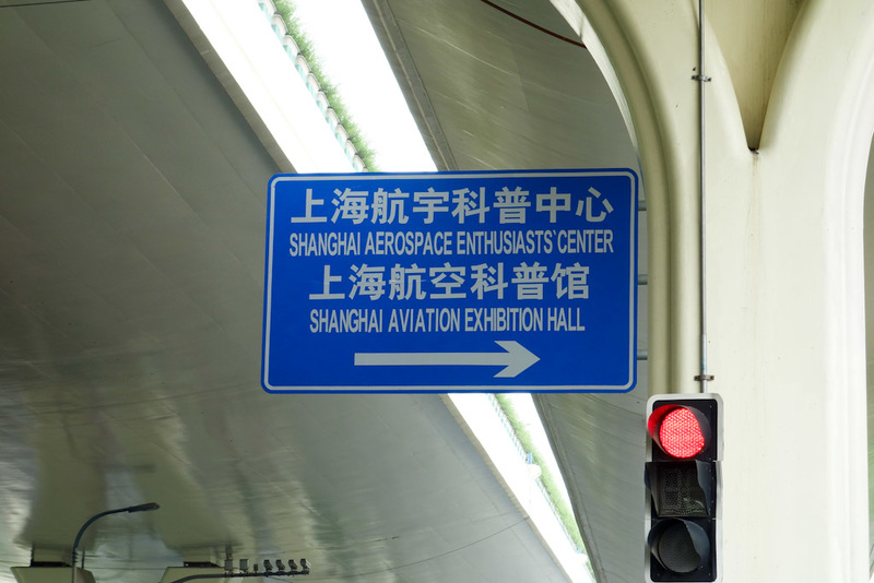 China-Shanghai-Museum-Amusement Park - This is the only sign, its under the elevated highway and points to a rather non descript gateway between apartment buildings. Its apparently not even