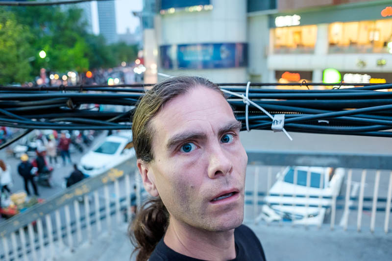 China-Zhengzhou-Food-Mall - This is my head, crossing the road on a pedestrian overpass, and becoming entangled in a huge mess of wires. They were no more than 5 feet above the w
