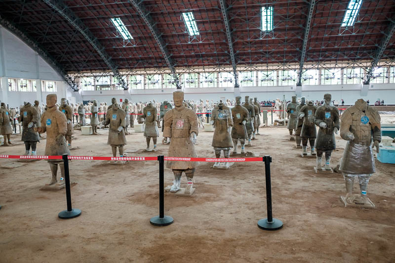 China-Xian-Terracotta Army - Some of them are covered in glad wrap. Many of them are put back together from pieces of broken pottery.