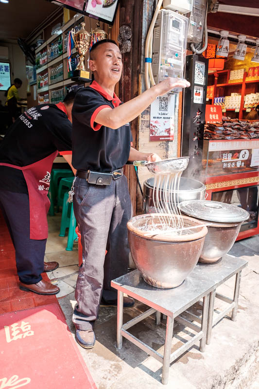 China-Chongqing-Ciqikou-Chilli - This guy puts on a song and dance show as he beats the fresh liquid noodles through the molecular sieve.