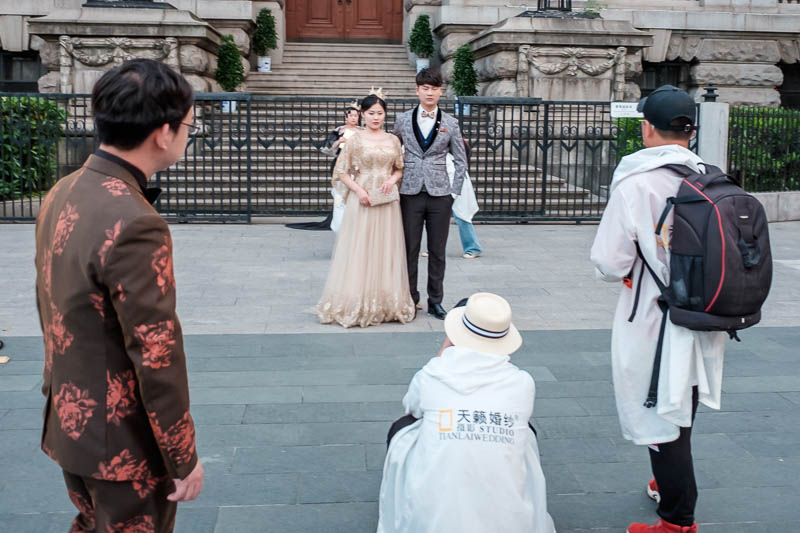 China-Wuhan-Pedestrian Street-Mall - Now its for brides in fetching dirty off brown dresses to pose in front of with cardboard gold crowns.