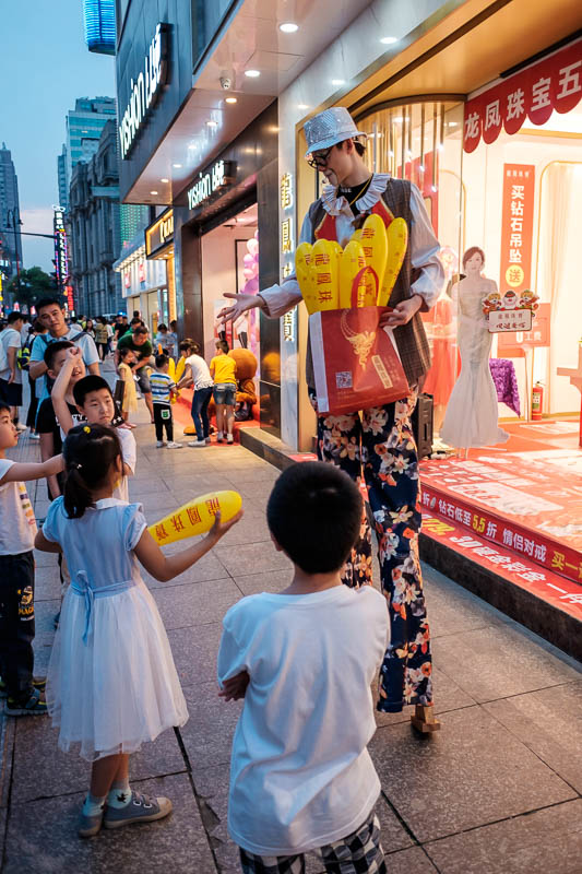 China-Wuhan-Pedestrian Street-Mall - There were lots of people on stilts doing things, this guys is playing rock paper scissors with children.