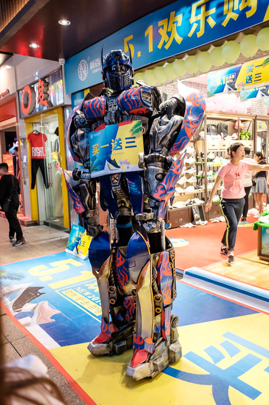 China-Wuhan-Pedestrian Street-Mall - As well as clowns on stilts, there were probably 5 giant transformers advertising out the front of stores. China loves giant robots.
