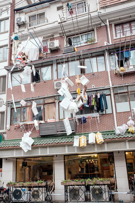 China-Shanghai-Zhujiajiao-Parrot - I am not sure what is going on here, someone has hung various pieces of polystyrene off their window where underpants would normally hang. Art / Rubbi