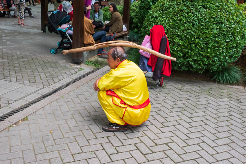 China-Shanghai-Park-Yuyuan Garden - If you get caught stepping on the sacred grass three times you are forced to put on a special yellow idiot suit and balance a stick on your head for 3
