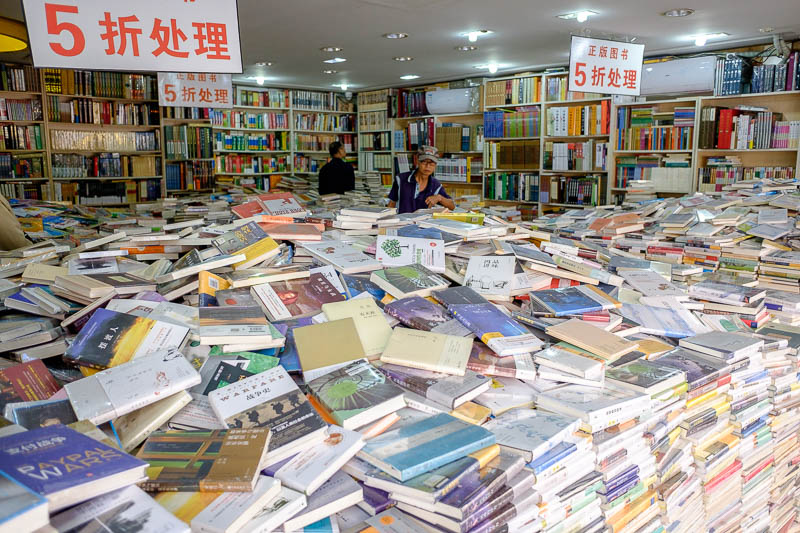 China-Shanghai-Maglev-Airport - Here is a Chinese bookshop. A truck backs up and pours books out. They must be presented this way by law, in the centre of each pile is a bundle of pe