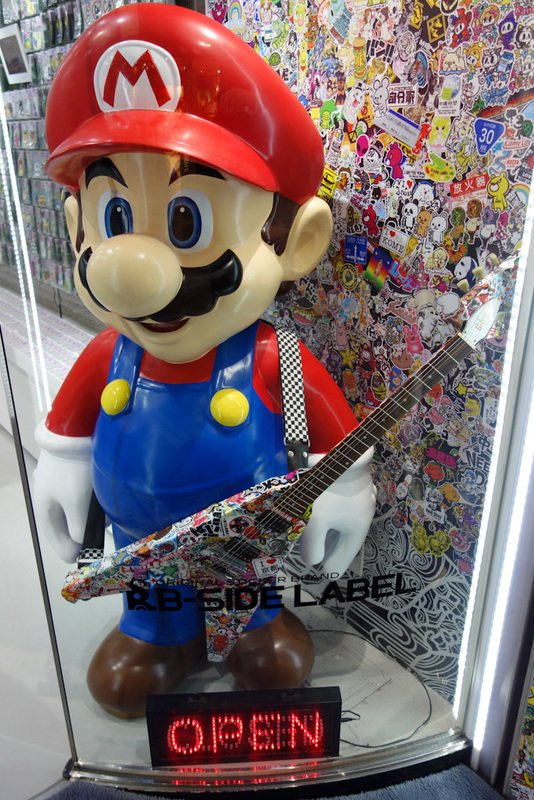 Japan-Kyoto-Shopping Street-Ramen - Super mario is holding a genuine Gibson Flying V. This is just a trading card shop, which has nothing to do with Nintendo or $2500 guitars.