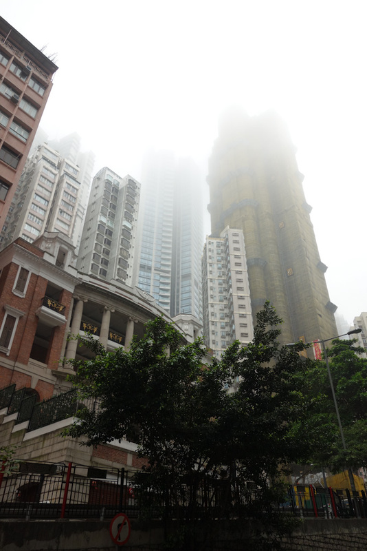 Hong Kong-The Peak-Fog - These buildings always amaze me, they are built on the side of a steep hill, seemingly designed to slide down the water logged slope whenever it next