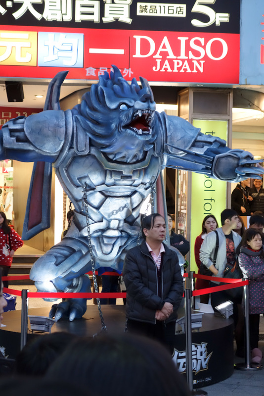 Taiwan-Taipei-Ximending-Shopping Street - Theres a huge crowd, except by this guy under the werewolf. He stands alone.