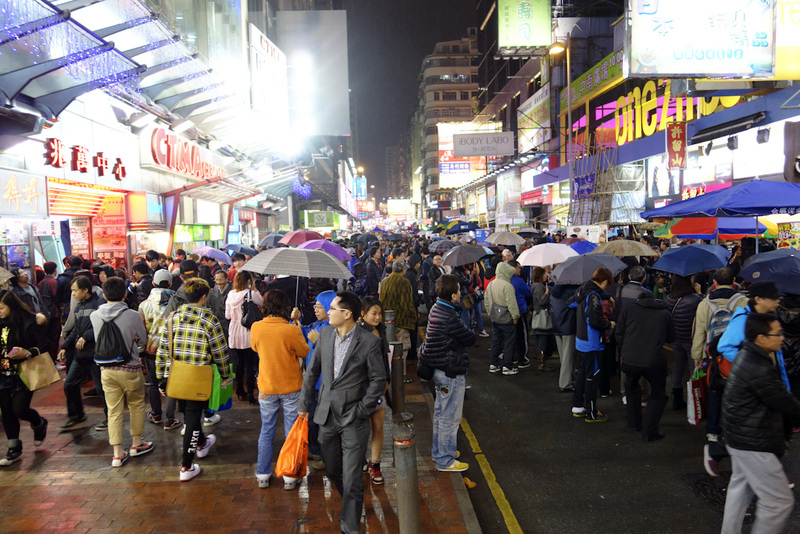 Hong Kong-Mall-Mong Kok - The Mong Kok electronics street that gets closed off every night and fills up with people, buskers, and children paid about $1 to hold cardboard signs