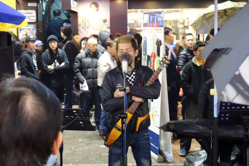 Hong Kong-Mall-Mong Kok - The buskers take it very seriously despite being terrible. This guy has a decent mic with pop filter, some sort of guitar that cost more than $10 and