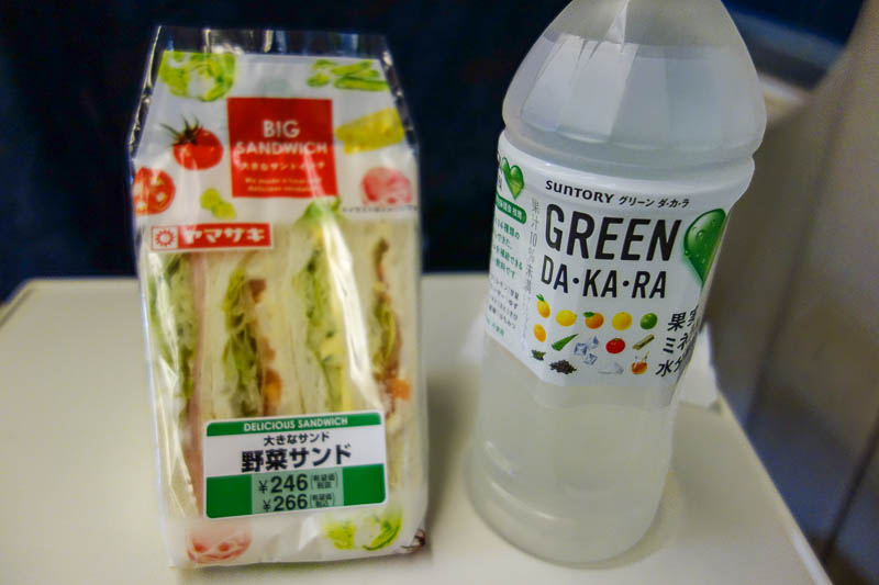 Japan-Hiroshima-Shimonoseki-Shinkansen - Time to enjoy my sandwich and lemon water. I have developed a real taste for white bread sandwiches with the crusts cut off. Mainly because of how che