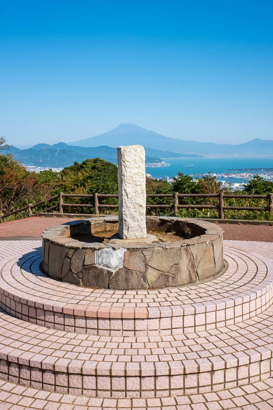 Japan-Shizuoka-Shrine-Kunozan Toshogu-Hiking - The summit marker, lined up with Fuji. The missing tile really bothers me more than it should. I suspect this is where everyone takes a photo, and eve