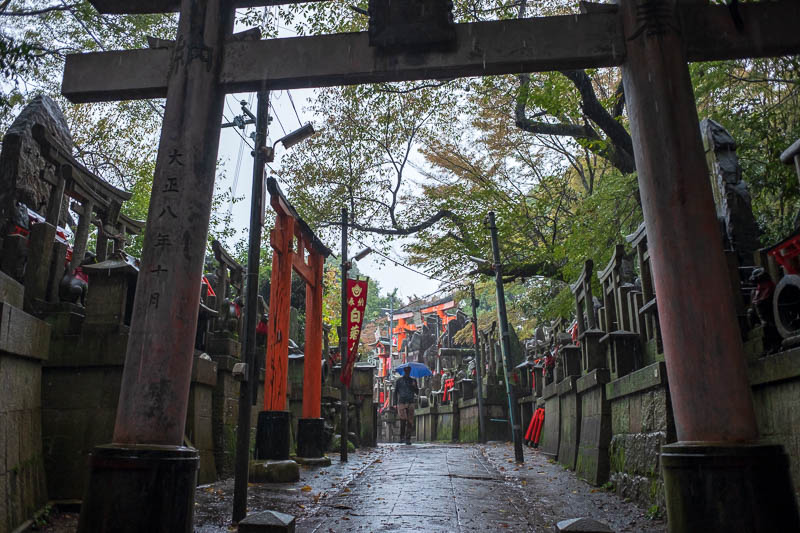 Japan-Kyoto-Fushimi Inari-Shrine-Rain - There are lots of little areas like this, with tea shops and vending machines, and lots of wires! However there are no toilets, there are signs explai