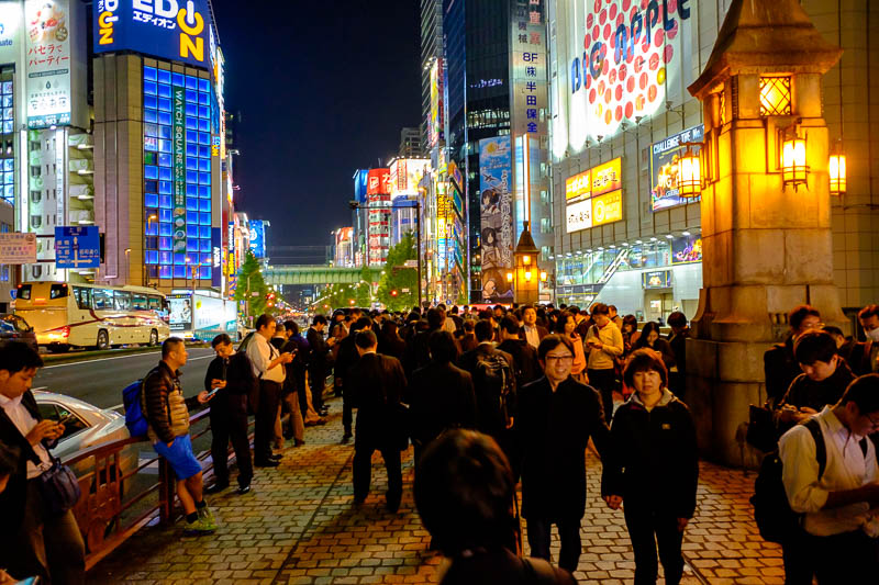 Japan-Tokyo-Akihabara-Ramen - These people are all standing around on a street corner kind of away from any shops. Almost underneath the highway overpass, all looking at their phon