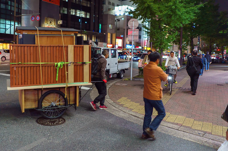 Japan-Fukuoka-Tenjin-Food - This guy is struggling to wheel his food cart across the road. At the same time, all the locals are waving hello to him, and hes putting it down to wa