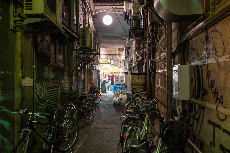 Japan-Tokyo-Ueno-Curry - Here are some bikes, some pipes, and a guy lit up by bright lights. Thats a new form of Haiku. Guy at the end of the alley was yelling loudly to himse