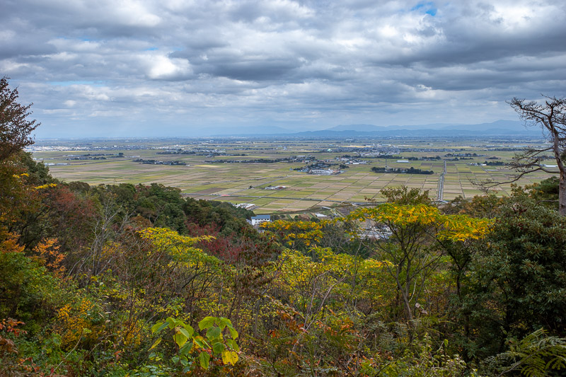 Japan-Niigata-Hiking-Mount Yahiko - I passed a number of mini shrines and graves on my way down. Heres a low down view looking back towards Niigata. A good spot to urinate I decided.
