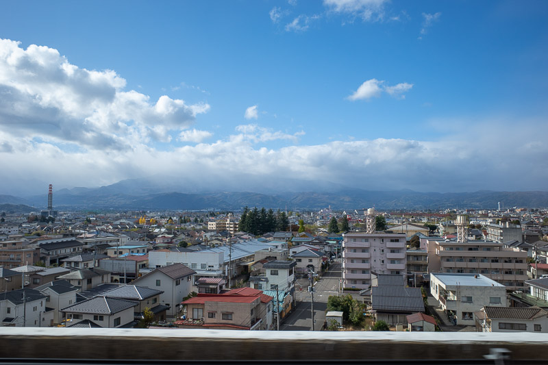 Japan-Yamagata-Koriyama-Shinkansen - Here is the view just out of Fukushima station, towards the mountains I would like to climb tomorrow. They are in cloud right now. Actually as I type