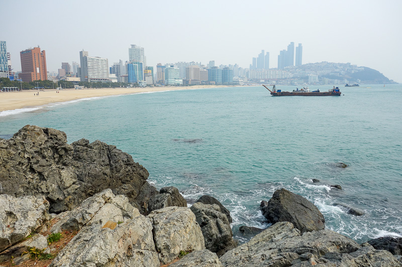 Korea-Busan-Beach-Haeundae - And looking back in the other direction, from the island thats not an island. The ships are doing stuff with the sand. Those tall buildings on the cli