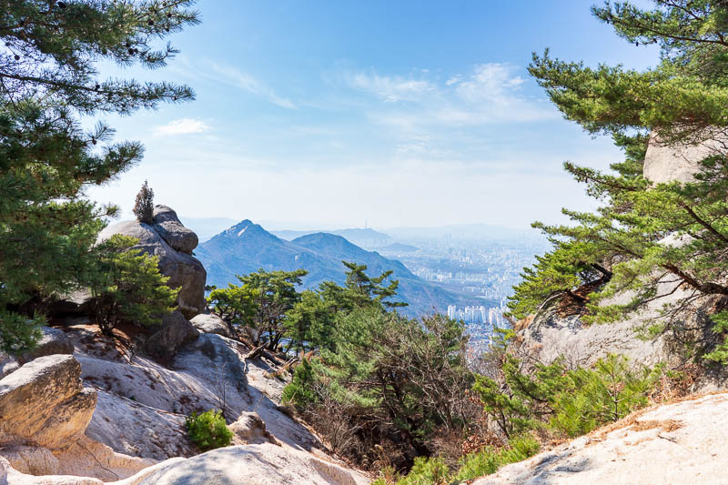 Korea-Hiking-Suraksan - Clearly I was enjoying taking photos of rocks contrasting against pine trees with the city in the background PUNCTUATED by an overly blue sky.