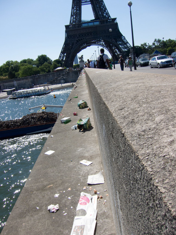 France-Paris-Arc de Triomphe-Eiffel Tower - Check out all the garbage on the bridge with the garbage barge going under? Whos responsible for keeping the streets clean here!!