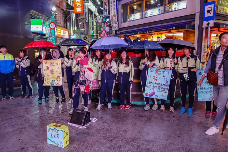 Taiwan-Taipei-Ximending-Ramen - These girls are protesting something with song. Their signs depict diamonds, hand bags, lipstick, and the King of Thailand? I cant read the traditiona